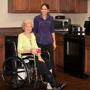 Woman in wheelchair stands next to her physical therapist during rehabilitation in Boone, North Carolina