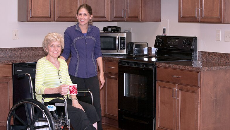Woman in wheelchair stands next to her physical therapist during rehabilitation